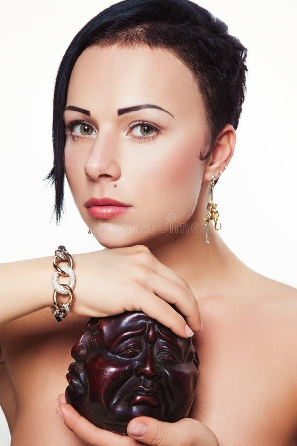 Giovane bella ragazza con l'acconciatura asimmetrica nella progettazione dei gioielli fotografia stock