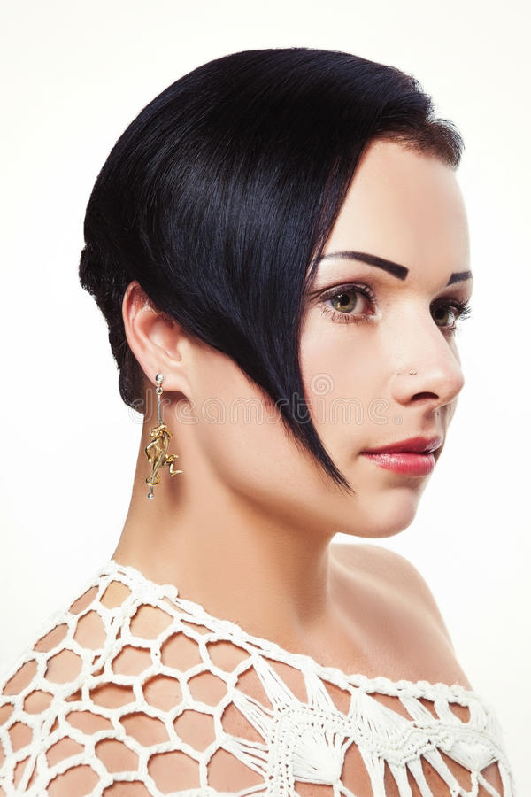 Giovane bella ragazza con l'acconciatura asimmetrica nella progettazione dei gioielli fotografia stock libera da diritti