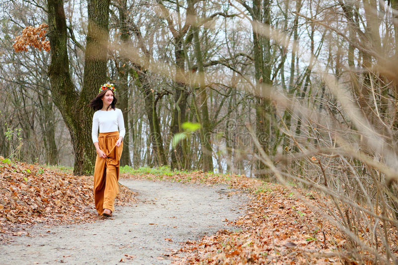 Giovane bella ragazza con la corona del fiore all'aperto nella foresta di autunno fotografie stock libere da diritti