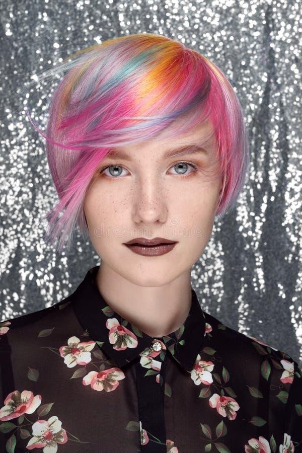 Giovane bella ragazza con le lentiggini. Capelli colorati, blu, giallo, rosso, lilla e rosa. Sfondo Pixie Bob Haircut Grey immagine stock libera da diritti