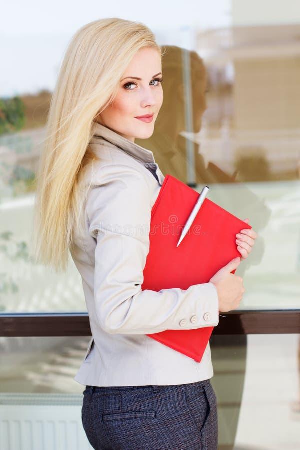 Giovane bella ragazza con una cartella rossa ed i libri fotografia stock libera da diritti