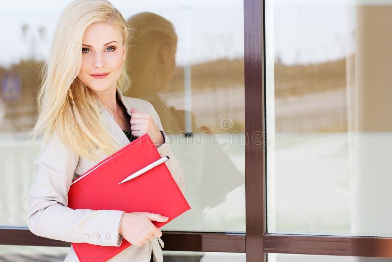 Giovane bella ragazza con una cartella rossa ed i libri fotografie stock libere da diritti