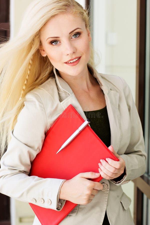 Giovane bella ragazza con una cartella rossa ed i libri immagine stock