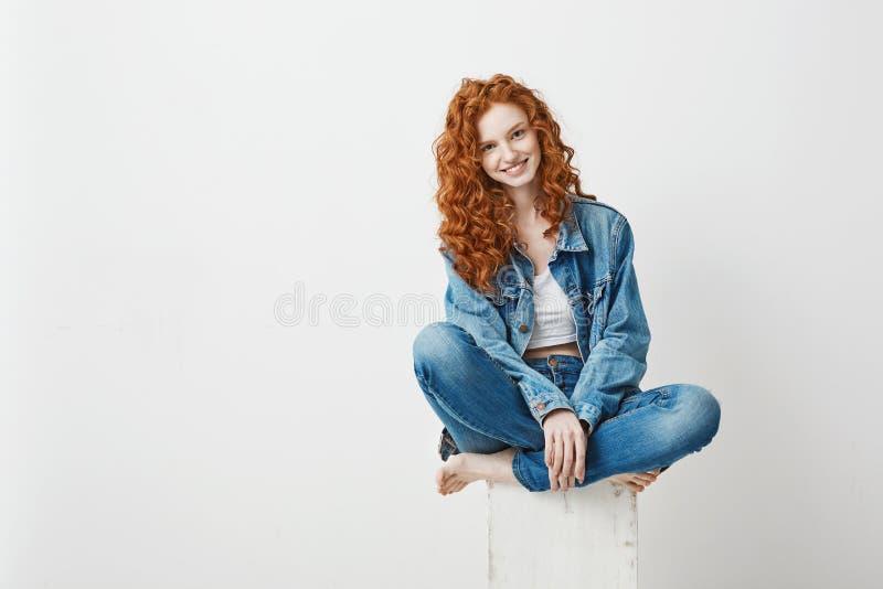 Giovane bella ragazza della testarossa che sorride esaminando macchina fotografica che si siede sulla scatola sopra fondo bianco  fotografie stock
