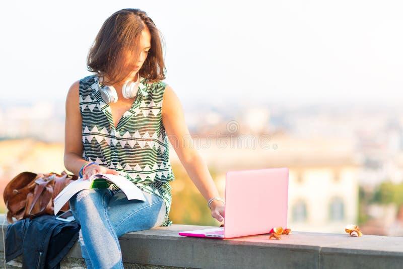 Giovane bella ragazza dello studente che studia con i libri ed il computer sopra fotografia stock