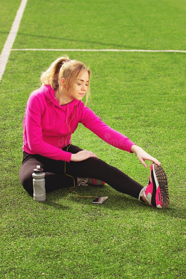 Giovane bella ragazza di forma fisica dei capelli biondi che fa allungamento sullo stadio Attività di sport di estate Erba verde  immagini stock libere da diritti