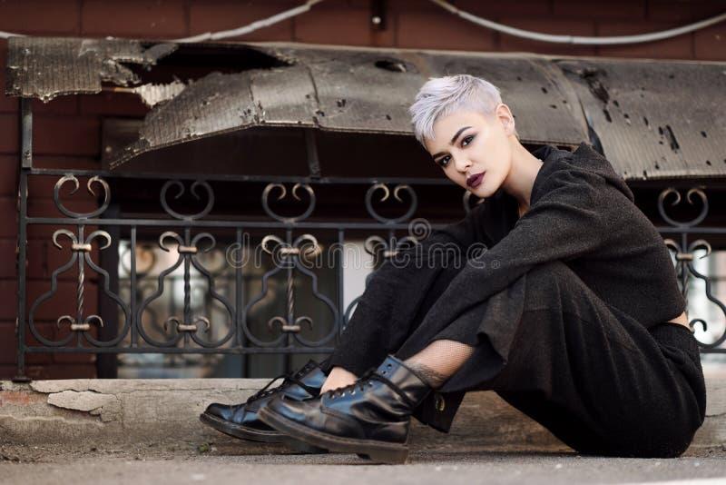Giovane bella ragazza di modo che spara all'aperto vicino al muro di mattoni alla casa fotografia stock libera da diritti