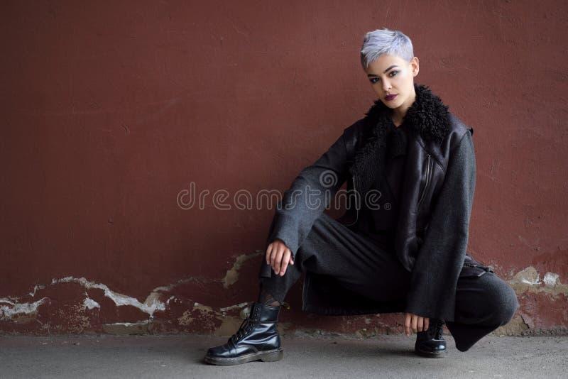 Giovane bella ragazza di modo che spara all'aperto vicino al muro di mattoni a casa immagini stock libere da diritti