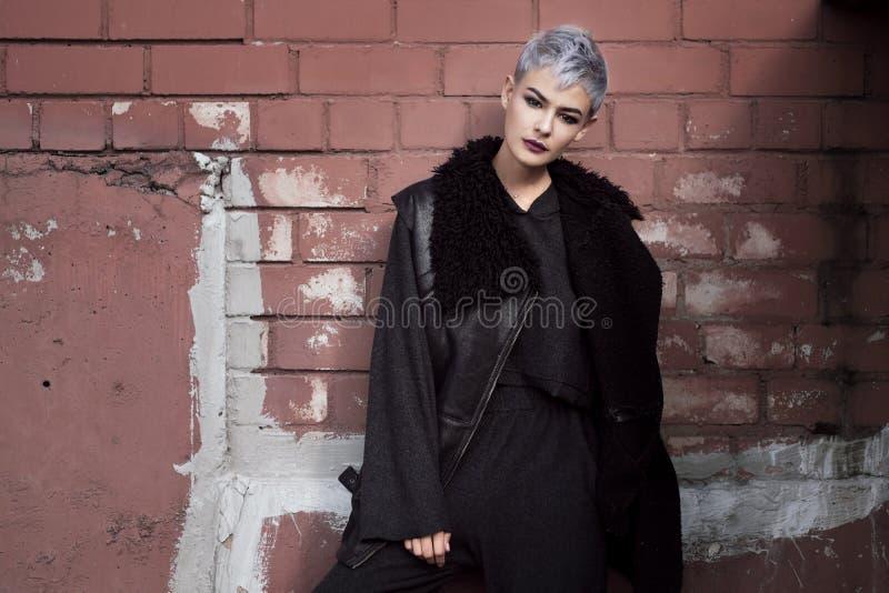 Giovane bella ragazza di modo che spara all'aperto vicino al muro di mattoni a casa immagini stock