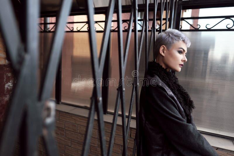 Giovane bella ragazza di modo che spara all'aperto vicino al muro di mattoni a casa fotografie stock libere da diritti