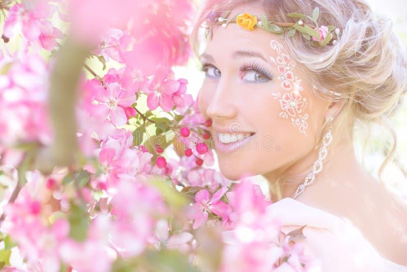Giovane bella ragazza elegante e attraente che stanno in un albero di fioritura vicino della foresta con capelli lunghi biondi ne fotografie stock libere da diritti