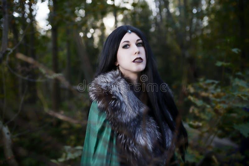 Giovane bella ragazza in impermeabile verde, sguardi come strega su Halloween in foresta immagini stock libere da diritti