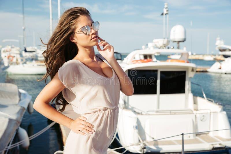 Giovane bella ragazza nei suglasses che stanno al pilastro del mare fotografia stock libera da diritti