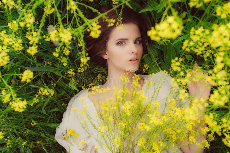 Giovane bella ragazza nel campo con i fiori gialli fotografie stock libere da diritti