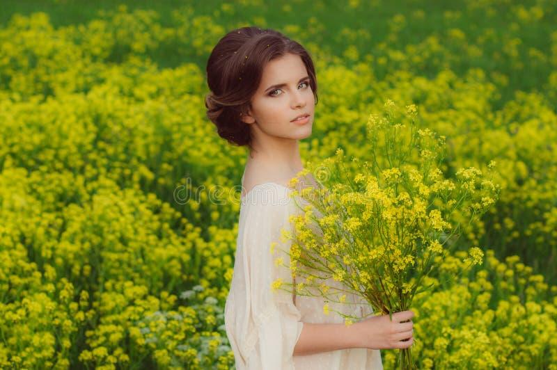 Giovane bella ragazza nel campo con i fiori gialli immagine stock libera da diritti