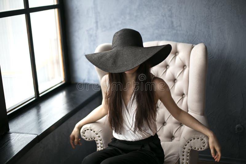 Giovane bella ragazza nel grande black hat La ragazza si siede elegante in una sedia bianca immagine stock