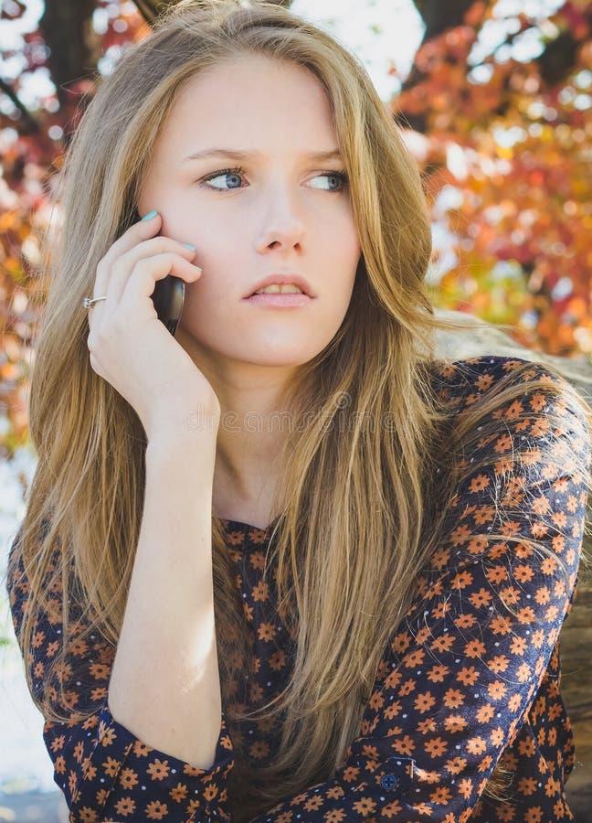 Giovane bella ragazza preoccupata che rivolge al telefono cellulare in parco immagine stock