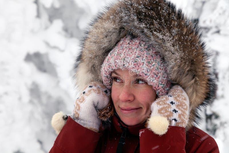 Giovane bella ragazza sorridente che guarda lateralmente in cappello tricottato rosa con il fiocchetto e guanti bianchi con il mo fotografia stock libera da diritti