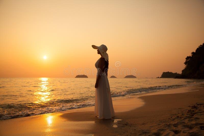 Giovane bella ragazza in un cappello bianco di paglia e del vestito su un tropica fotografia stock