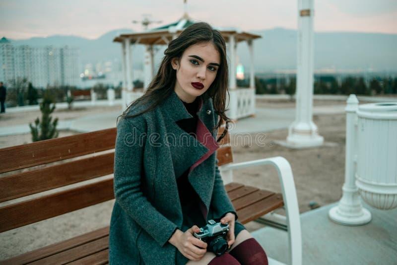 Giovane bella ragazza in un cappotto grigio con le pose d'annata della macchina fotografica nella sera immagini stock libere da diritti