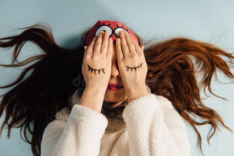 Giovane bella ragazza in un maglione con un cervo e una maschera di sonno che si riposa sul fondo bianco immagini stock