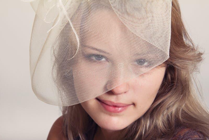 Giovane bella ragazza in velo beige fotografie stock