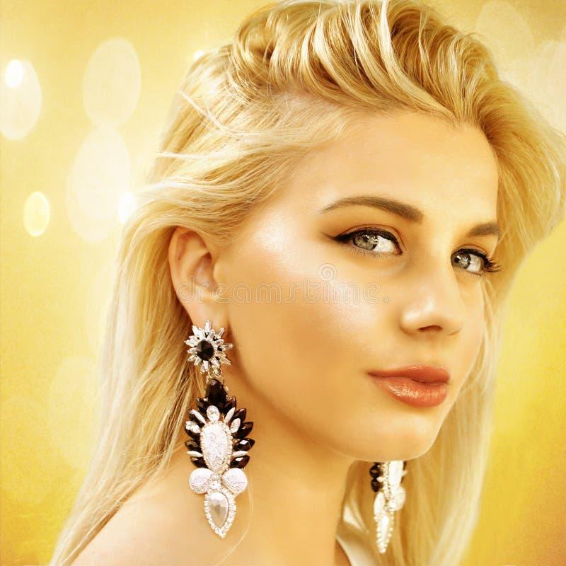 Giovane bella ragazza in vetri di sole con i grandi orecchini su un fondo astratto dell'oro fotografie stock