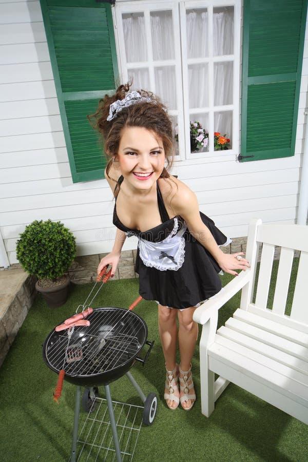 Giovane bella salsiccia della frittura della cameriera sull'addetto alla brasatura fotografie stock