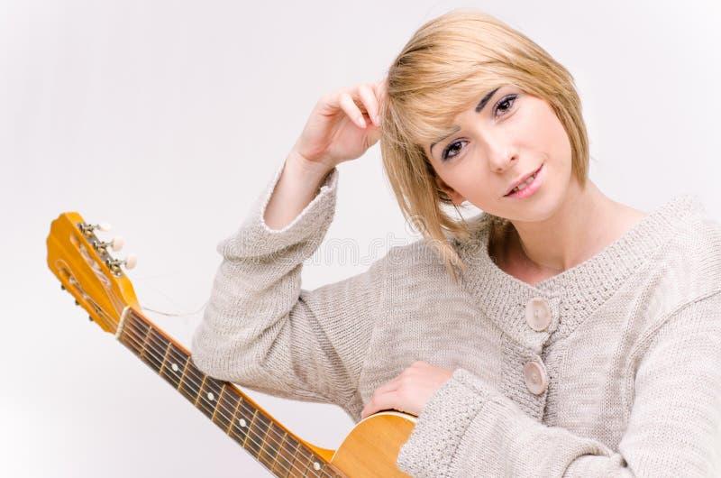 Giovane bella signora bionda sorridente in maglione grigio che gioca chitarra acustica immagine stock