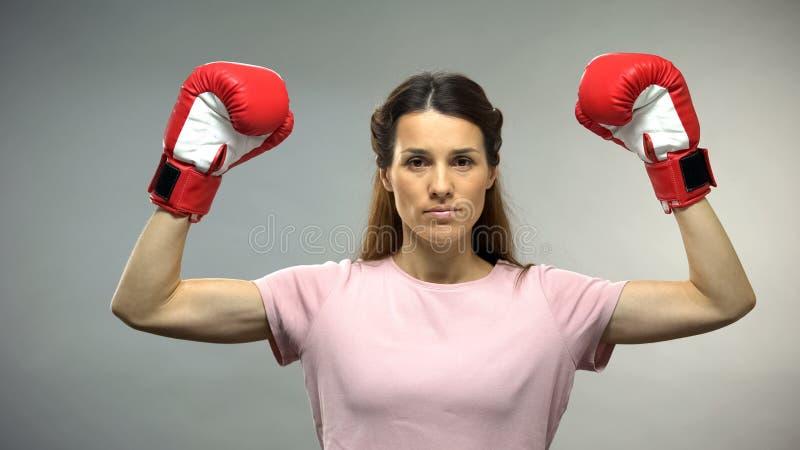 Giovane bella signora in guantoni da pugile che sollevano le mani su, superstite del cancro, concetto fotografia stock