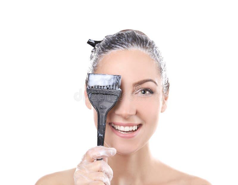 Giovane bella spazzola della tenuta della donna con tintura per capelli immagine stock