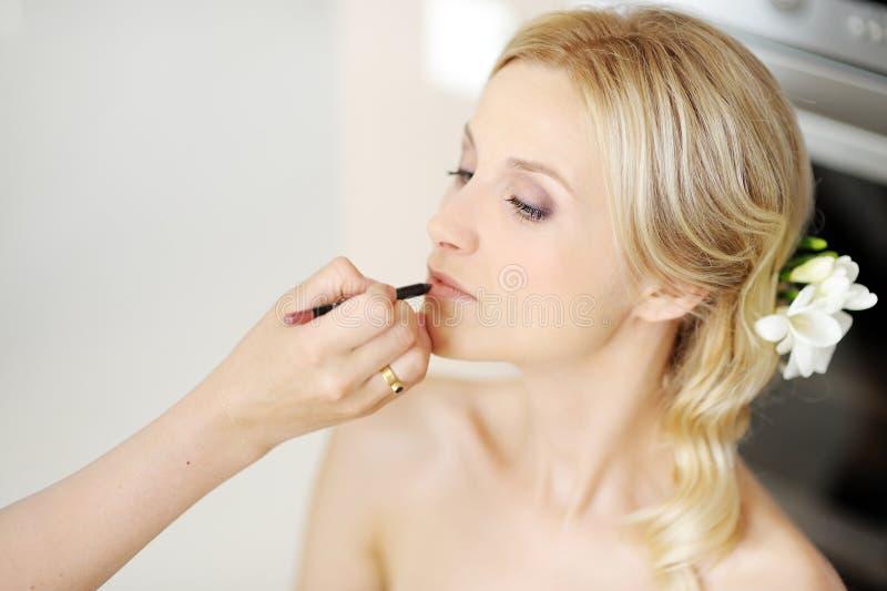 Giovane bella sposa che applica trucco di cerimonia nuziale immagine stock
