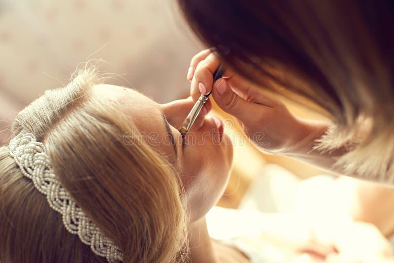 Giovane bella sposa che applica trucco di cerimonia nuziale immagine stock libera da diritti