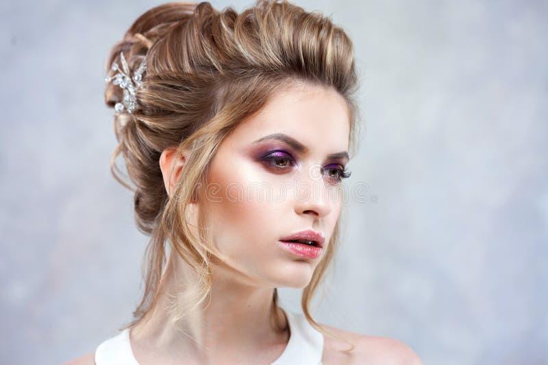Giovane bella sposa con un'alta pettinatura elegante Acconciatura di nozze con l'accessorio in suoi capelli fotografie stock