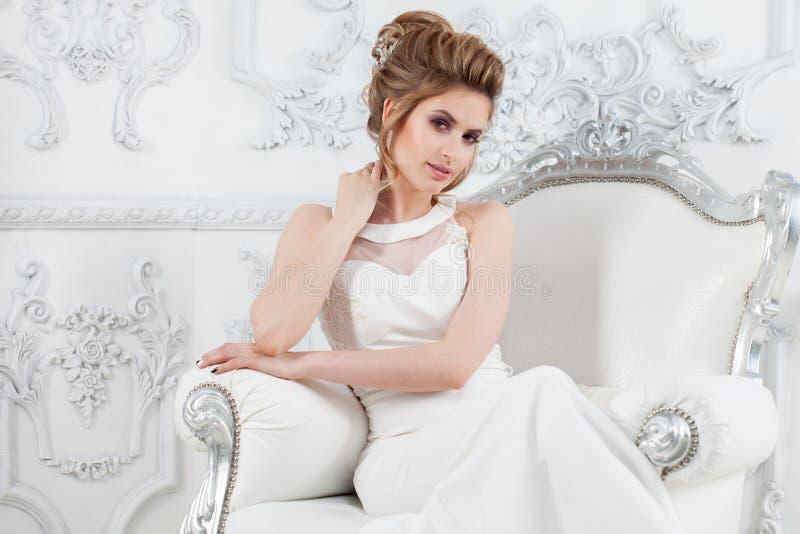 Giovane bella sposa con un'alta pettinatura elegante Sposa elegante nell'interno lussuoso, sedentesi su una sedia immagine stock libera da diritti