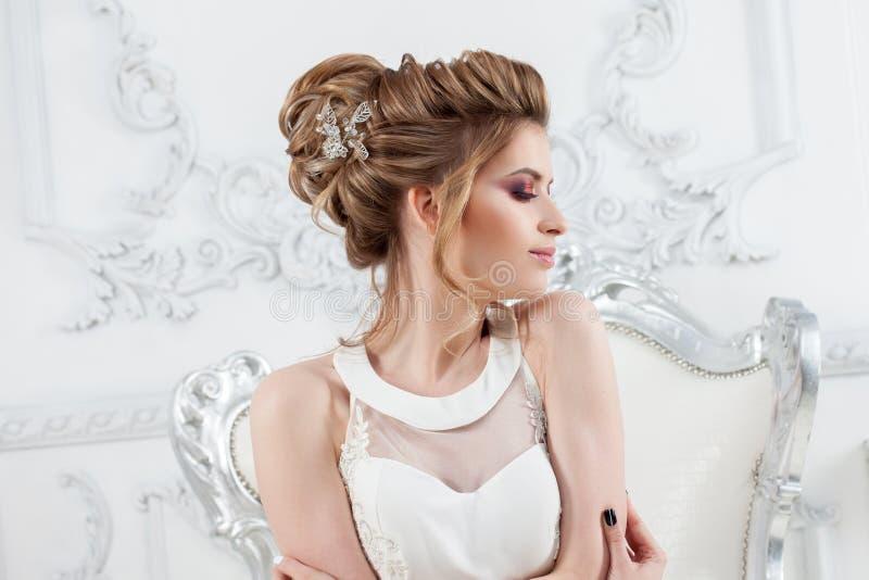 Giovane bella sposa con un'alta pettinatura elegante Sposa elegante nell'interno lussuoso, sedentesi su una sedia fotografie stock
