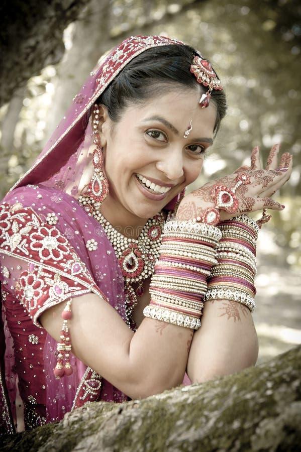 Giovane bella sposa indù indiana che ride sotto l'albero con le mani dipinte sollevate immagini stock libere da diritti