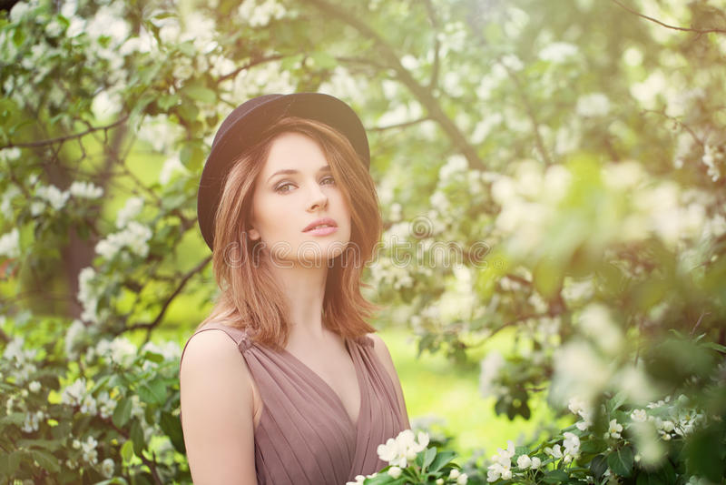 Giovane bellezza nella luce solare di primavera Donna in buona salute sul fiore fotografia stock libera da diritti