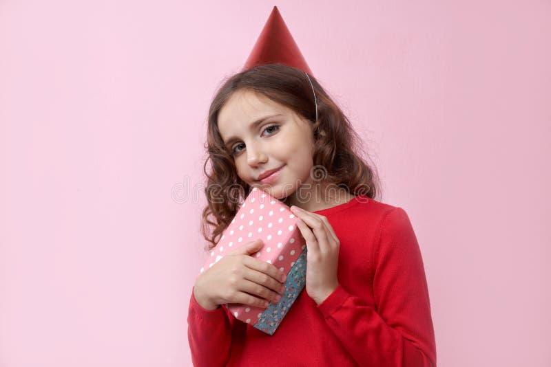 Giovane bello adolescente sorridente della ragazza che posa per un ritratto su fondo isolato in un maglione rosso fotografia stock