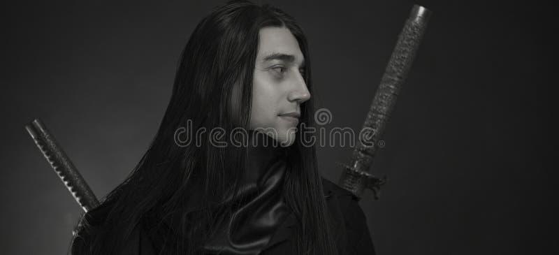 Giovane bello alla moda con la spada giapponese di katana Il ritratto dell'uomo caucasico immagini stock