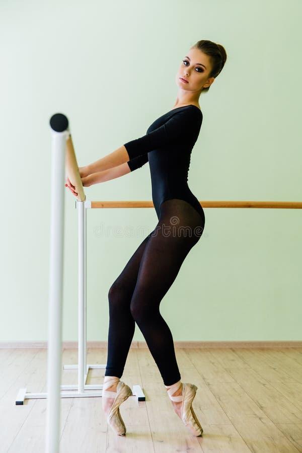 Giovane bello ballerino che posa nella barra di balletto di spirito dello studio sulla punta dei piedi Castana sexy moderno immagini stock