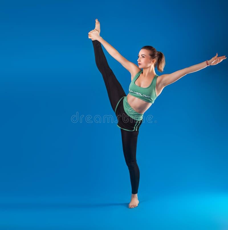 Giovane bello ballerino che posa sul fondo blu isolato dello studio fotografie stock