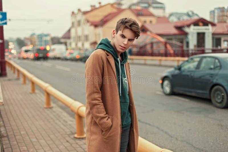 Giovane bello in cappotto e maglia con cappuccio che posa sulla via fotografia stock libera da diritti