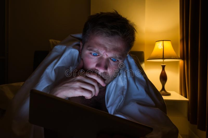 Giovane bello a casa che legge con il PC della compressa che si trova sul letto alla notte È stanco e vuole dormire immagini stock libere da diritti