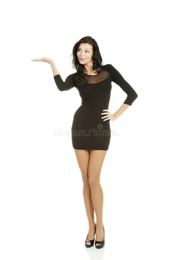 Donna in vestito sexy che mostra lo spazio della copia immagine stock
