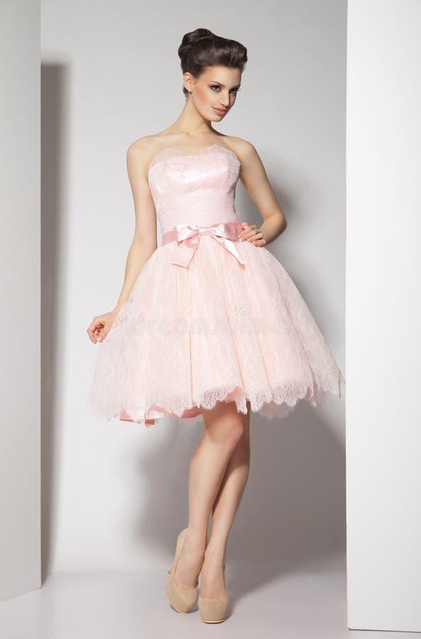 Giovane bello castana in vestito rosa su bianco immagini stock libere da diritti