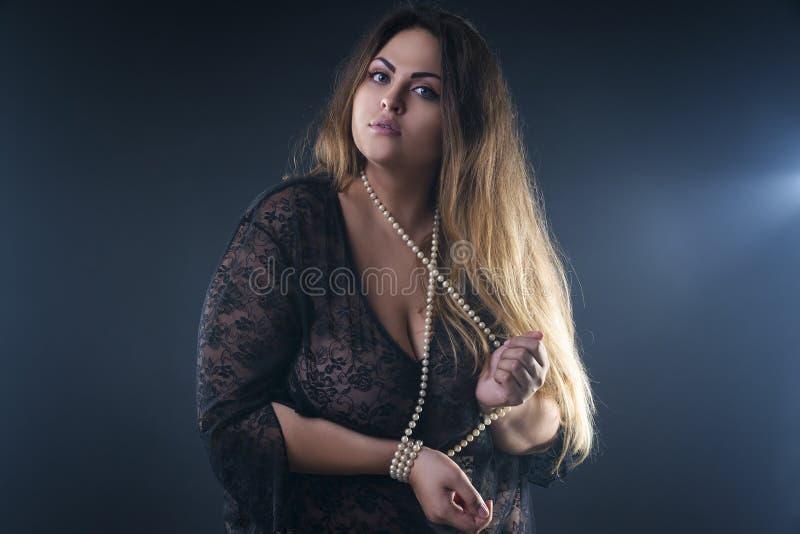 Giovane bello caucasian più il modello di dimensione, donna del xxl nel peignoir nero su fondo fumoso fotografie stock