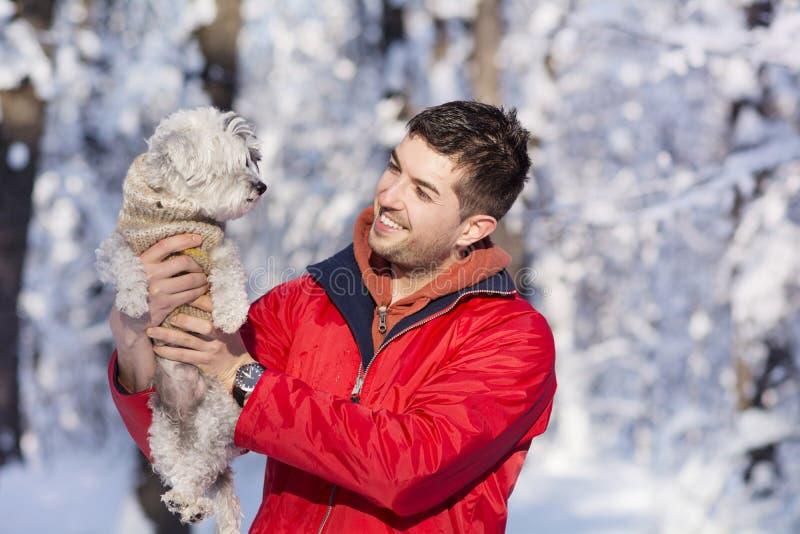 Giovane bello che abbraccia il suo piccolo cane bianco nell'inverno nevicare fotografia stock