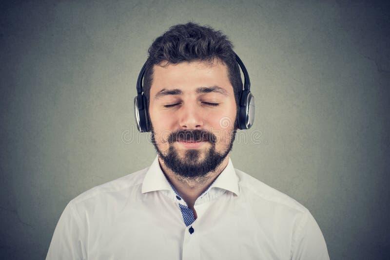 Giovane bello che ascolta le cuffie d'uso di musica immagini stock