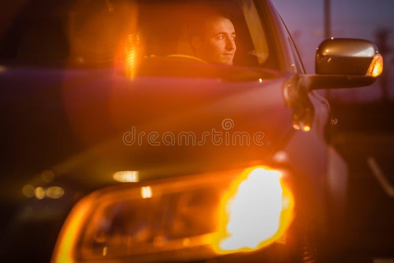 Giovane bello che conduce la sua automobile alla notte immagine stock libera da diritti